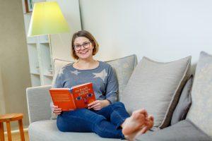 Frau Gessmann mit einem orangen Buch in der Hand relaxed auf dem Sofa, das Bild steht z.B. für Stresskompetenz, Balance, Entspannung