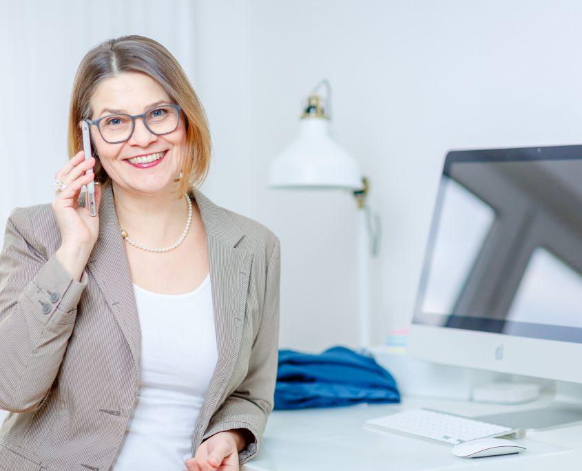 Kontakt - Frau Gessmann mit Telefon am Ohr, Situation am Stehschreibtisch mit Bildschirm und Tastatur